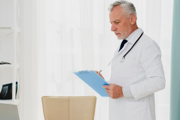 Doctor writing on clipboard Free Photo