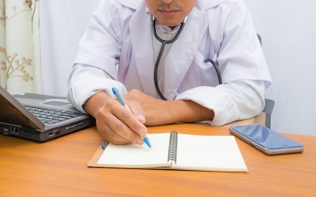 Doctor writing note book on pattern table, Premium Photo