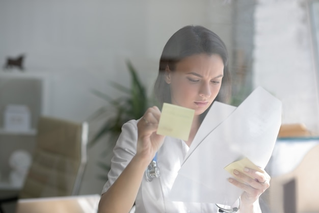 Doctor writing patient test results on board Premium Photo