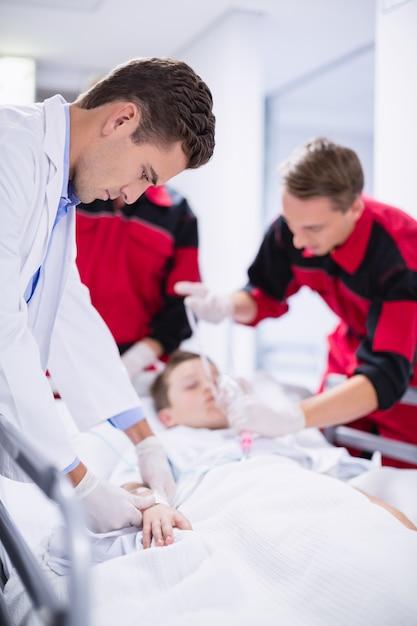 Medici che regolano la maschera di ossigeno mentre si precipitano il paziente in pronto soccorso Foto Gratuite