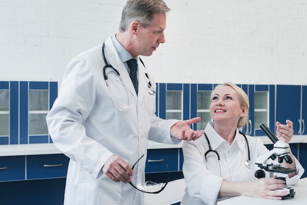 Doctors analyzing with a microscope Free Photo