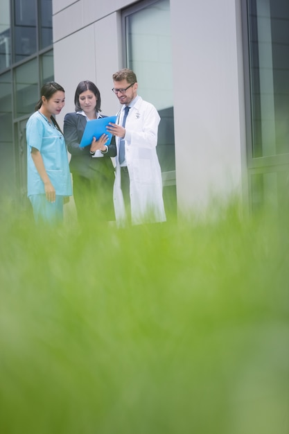 Врачи и медсестра обсуждают отчет Бесплатные Фотографии