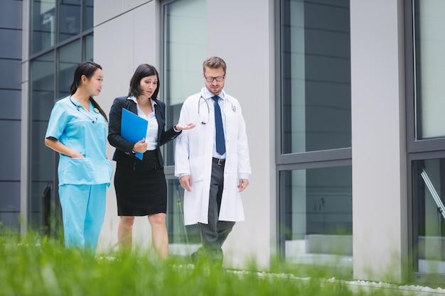 Врачи и медсестра взаимодействуют во время прогулки Бесплатные Фотографии
