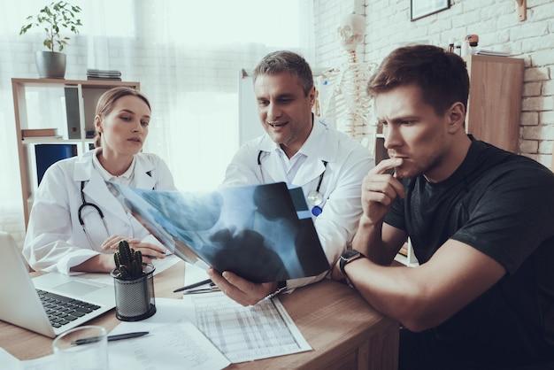 의사는 운동 선수에게 엑스레이를 보여주고 있습니다. 프리미엄 사진