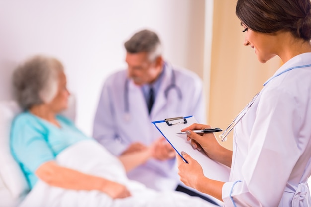 Doctors are standing in front of an elderly grandmother. Premium Photo