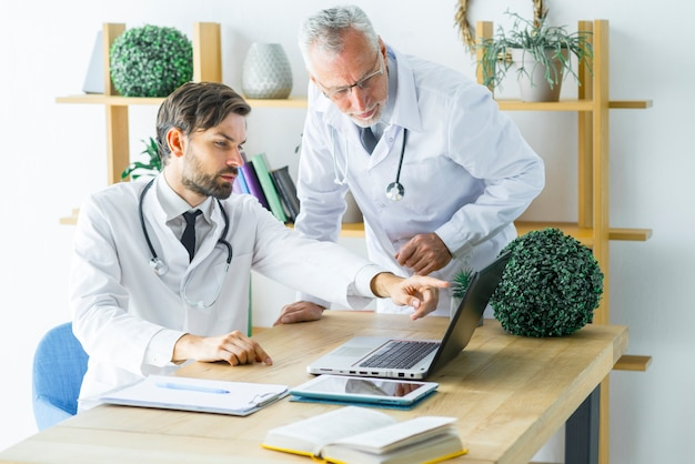 Doctors discussing data on laptop Free Photo
