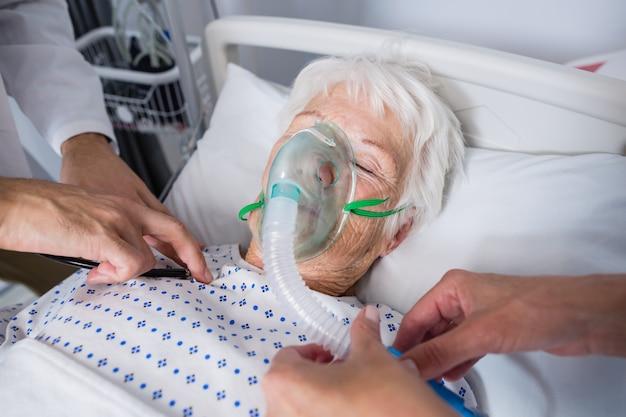Doctors examining senior patient with stethoscope Free Photo