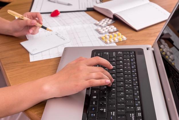 Doctors hands typing on laptop and filling prescription Premium Photo