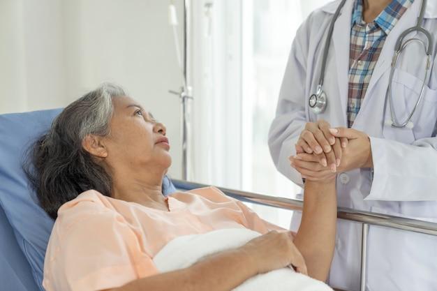 Врачи держатся за руки, чтобы поощрить пожилых женщин-пациентов в концепции больницы и старших женщин в области медицины и здравоохранения Бесплатные Фотографии