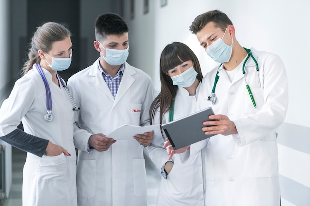 Doctors in masks using tablet Free Photo