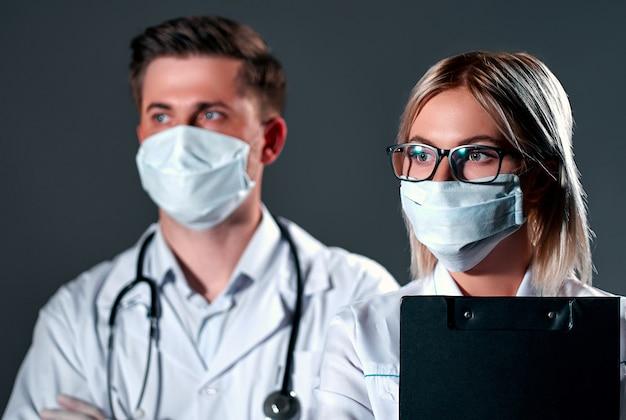 防護マスクと暗い灰色の背景に手袋の医師 Premium写真