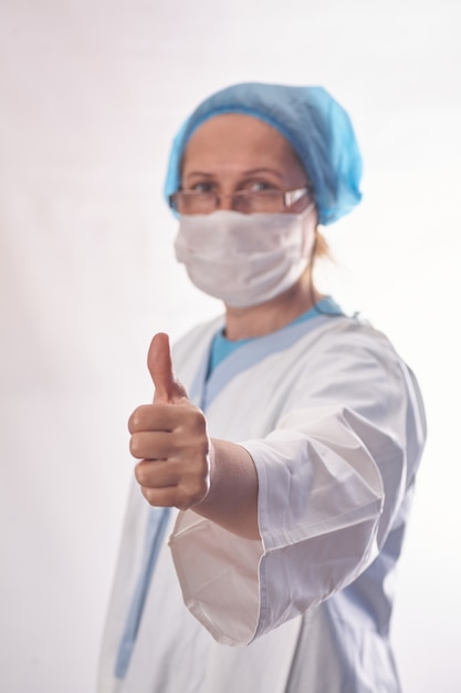 医師、感染症、研究、covid19のコンセプト。満足している若い女性医師は、ウイルスの研究で良い結果を受け取り、ワクチンを発見し、親指を立てる、フェイスマスクを着用する Premium写真