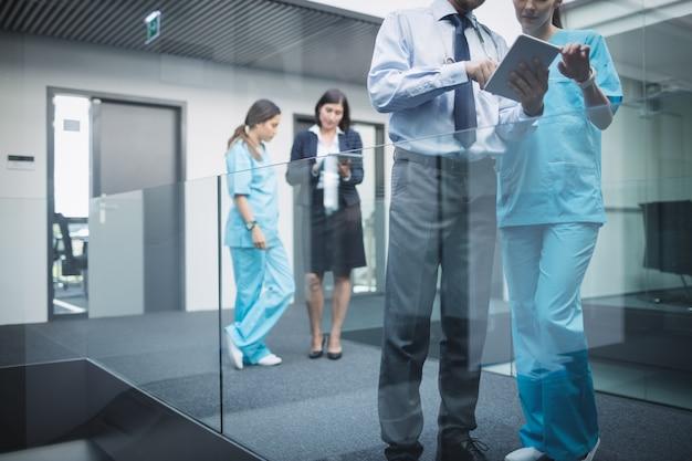 Medici e infermieri che discutono su tavoletta digitale Foto Gratuite