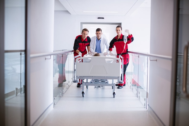 Doctors pushing emergency stretcher bed in corridor Free Photo