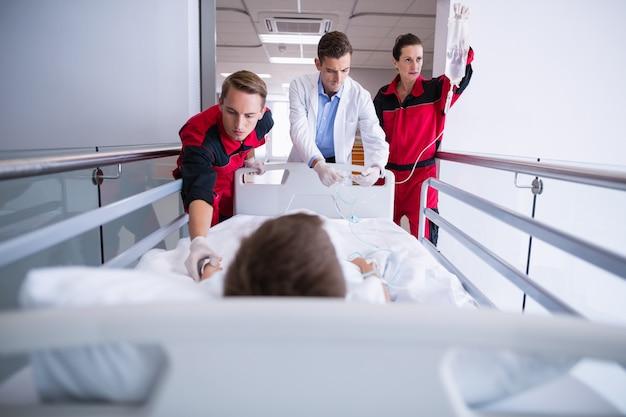 Medici spingendo il letto della barella di emergenza in corridoio Foto Gratuite