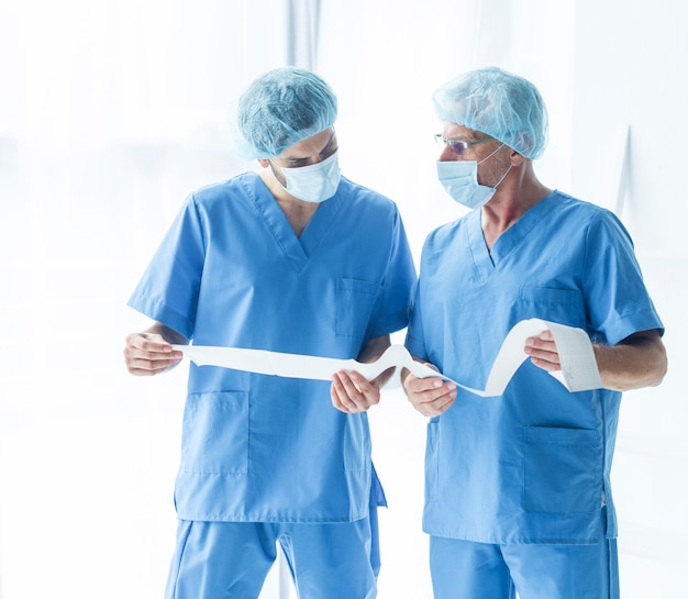 Doctors in scrubs reading test results Free Photo