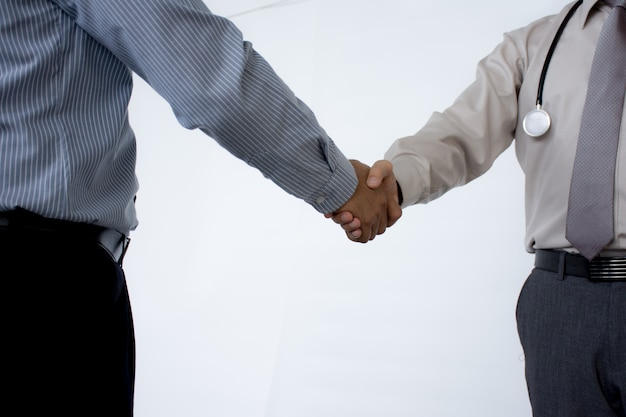 Doctors shaking hands to each other finishing up medical meeting  isolated on gray background. Premium Photo