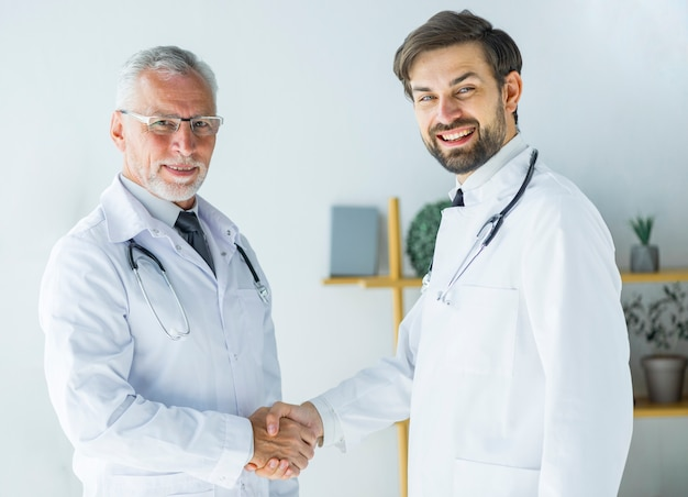 Doctors shaking hands and looking at camera Free Photo