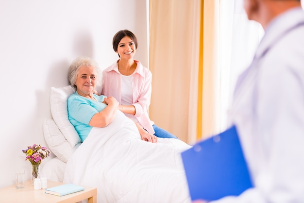 Doctors take care of an old woman in a clinic. Premium Photo
