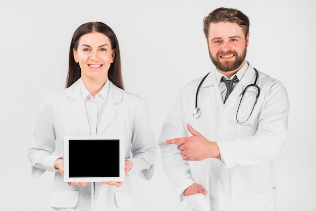 Doctors woman and man showing tablet Free Photo