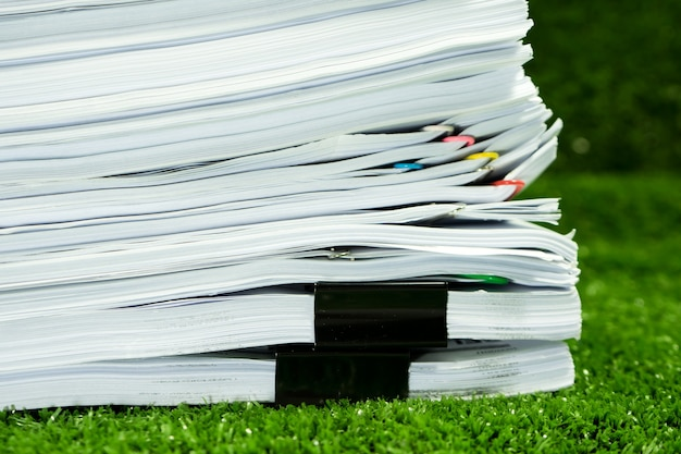 Documents pile on grass in concept save earth and use paper economically Premium Photo
