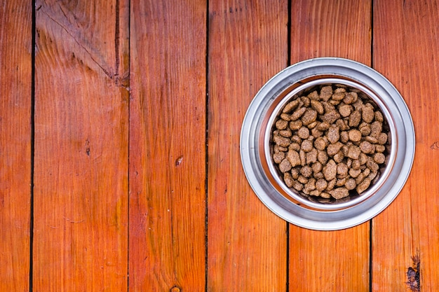 Dog food bowl on wooden background with copy space Free Photo