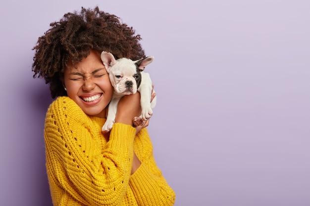 犬の飼い主と彼女のペット。幸せな民族の巻き毛の女の子は、顔の近くにかわいい子犬を抱き、家畜への愛と思いやりを表現し、好きな品種の犬を購入し、笑い、喜びで目を閉じています 無料写真