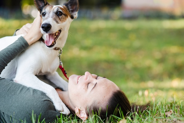 Dog playing with woman in grass Free Photo
