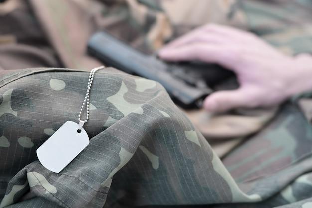 ドッグタグは、銃で自殺するうつ病の男性の手にあります。痛みに耐えられなくなったベテランのコンセプトは、自殺を決意する。 Premium写真