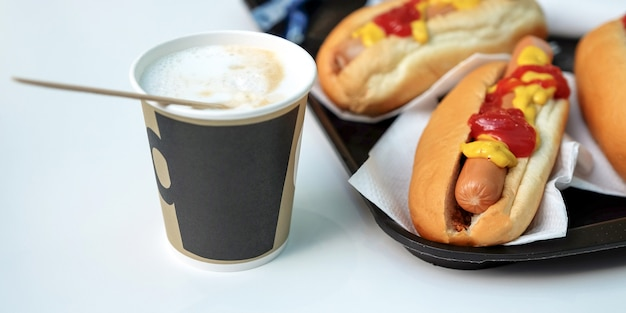 The-dogs, sauce, ketchup, coffee with milk in a cup. latte Premium Photo