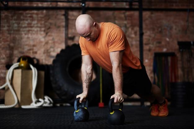 Doing push-ups in modern gym Free Photo