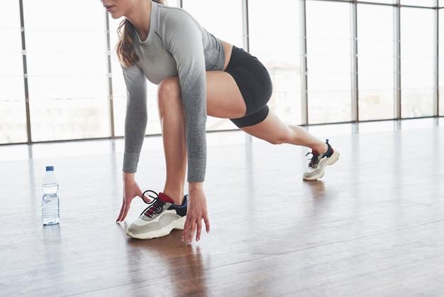 Приседания. спортивная молодая женщина имеет фитнес-день в тренажерном зале в утреннее время Бесплатные Фотографии