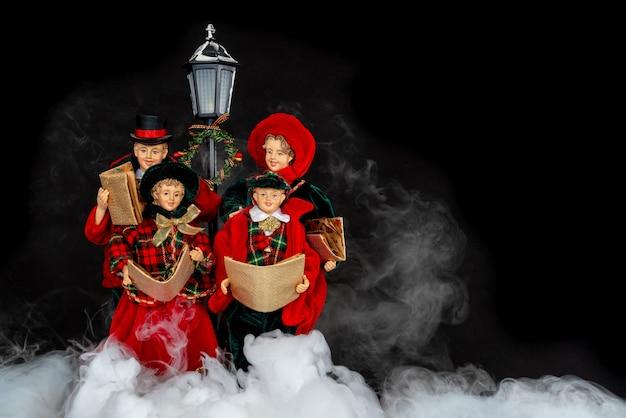Семья кукол поет рождественские гимны в ночном тумане. Premium Фотографии