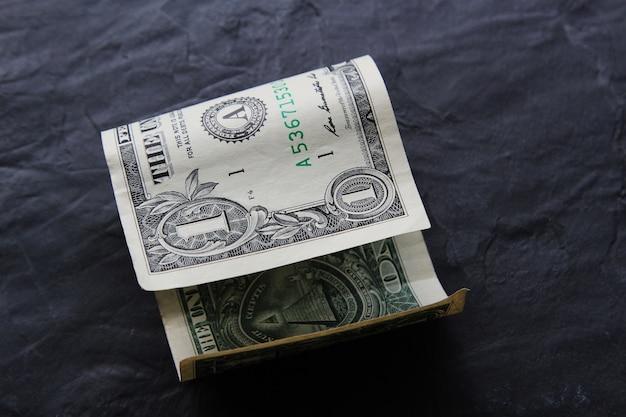Fattura del dollaro su una superficie nera Foto Gratuite
