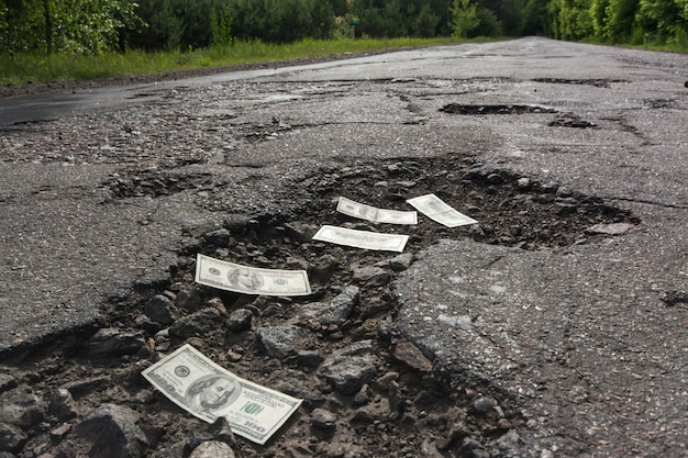 Dollar bills in the potholes on road Premium Photo
