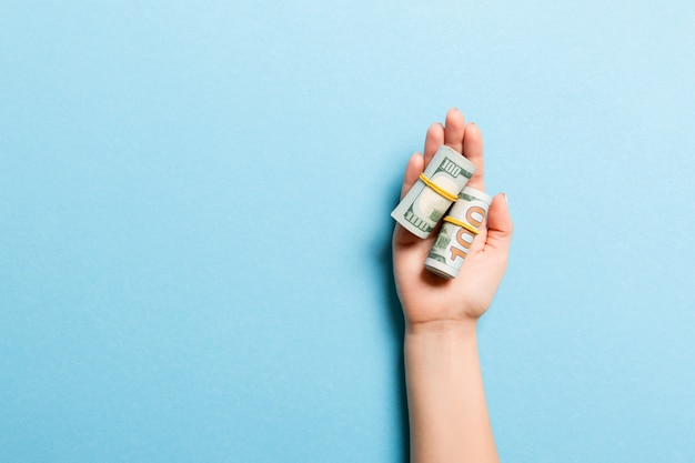 Dollar bills rolled up in tubes in female palm Premium Photo