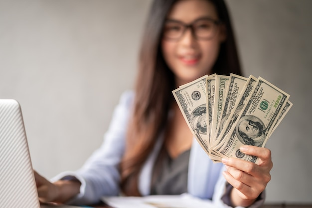 Premium Photo   Dollar in a businesswoman hand. an asian woman is working  from home or office and glad to get dollar money from work and from a  supplementary career or part-time