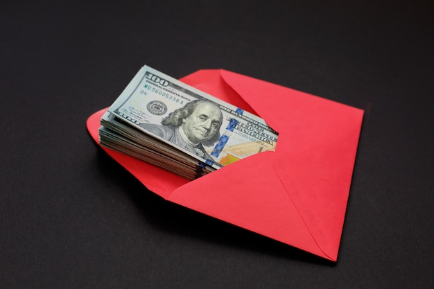 Dollar money in the red envelope on black background bonus, reward, benefits concept. Premium Photo