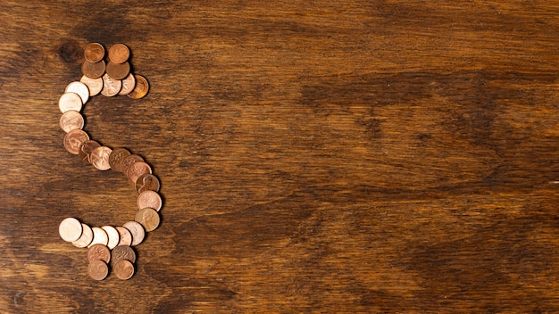 Dollar sign made out of coins on copy space wooden background Free Photo