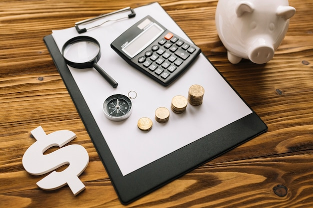 Dollar sign and piggybank with clipboard on wooden desk Free Photo