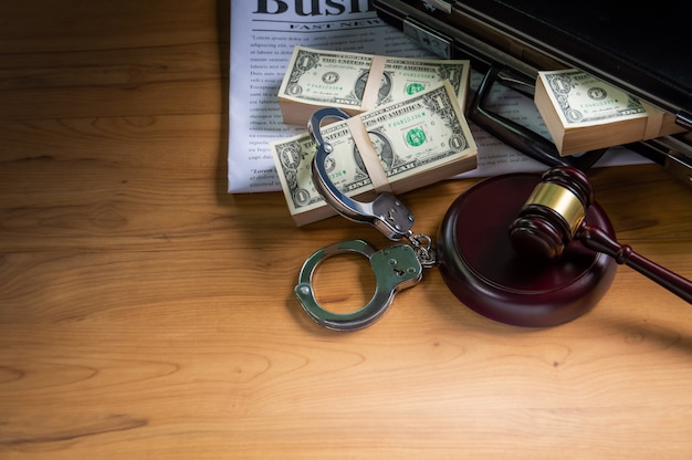 Dollars in briefcase handcuff put on a business newspaper and wooden hammer for a trial. Premium Photo