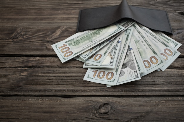 Доллары в черном кошельке на старых деревянных фоне Premium Фотографии