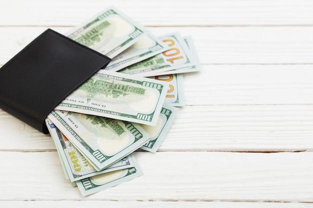 Доллары в черном кошельке на белой деревянной доске Premium Фотографии