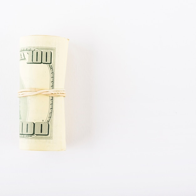 Dollars rolled into tube on white background Free Photo