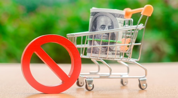 Dollars in a shopping cart and sign of prohibition Premium Photo