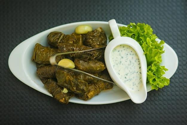 Dolma. matsoni white sauce with garlic and herbs. Premium Photo