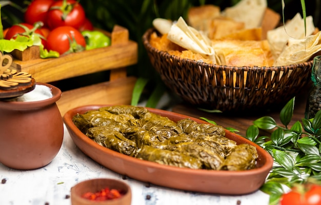 Dolma (tolma, sarma) - stuffed grape leaves with rice and meat. on kitchen table with yogurt, bread, vegetables. traditional caucasian, ottoman, turkish and greek cuisine Free Photo