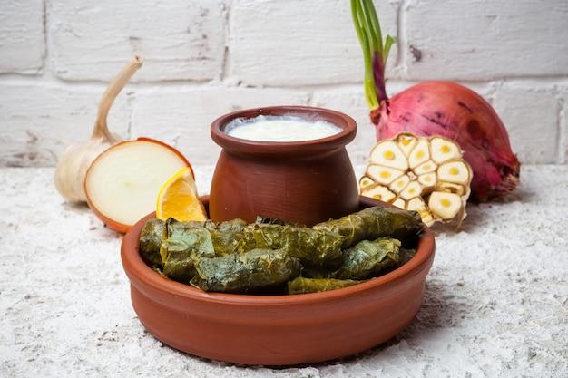 Dolma con yogurt e pentola di terracotta e cipolla e aglio in piatti di terracotta Foto Gratuite