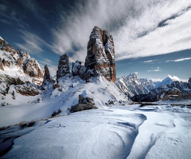 Dolomiti coperte di neve sotto la luce del sole e un cielo nuvoloso nelle alpi italiane in inverno Foto Gratuite