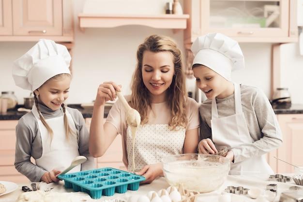 Domestic baking liquid dough into cupcake pan. Premium Photo